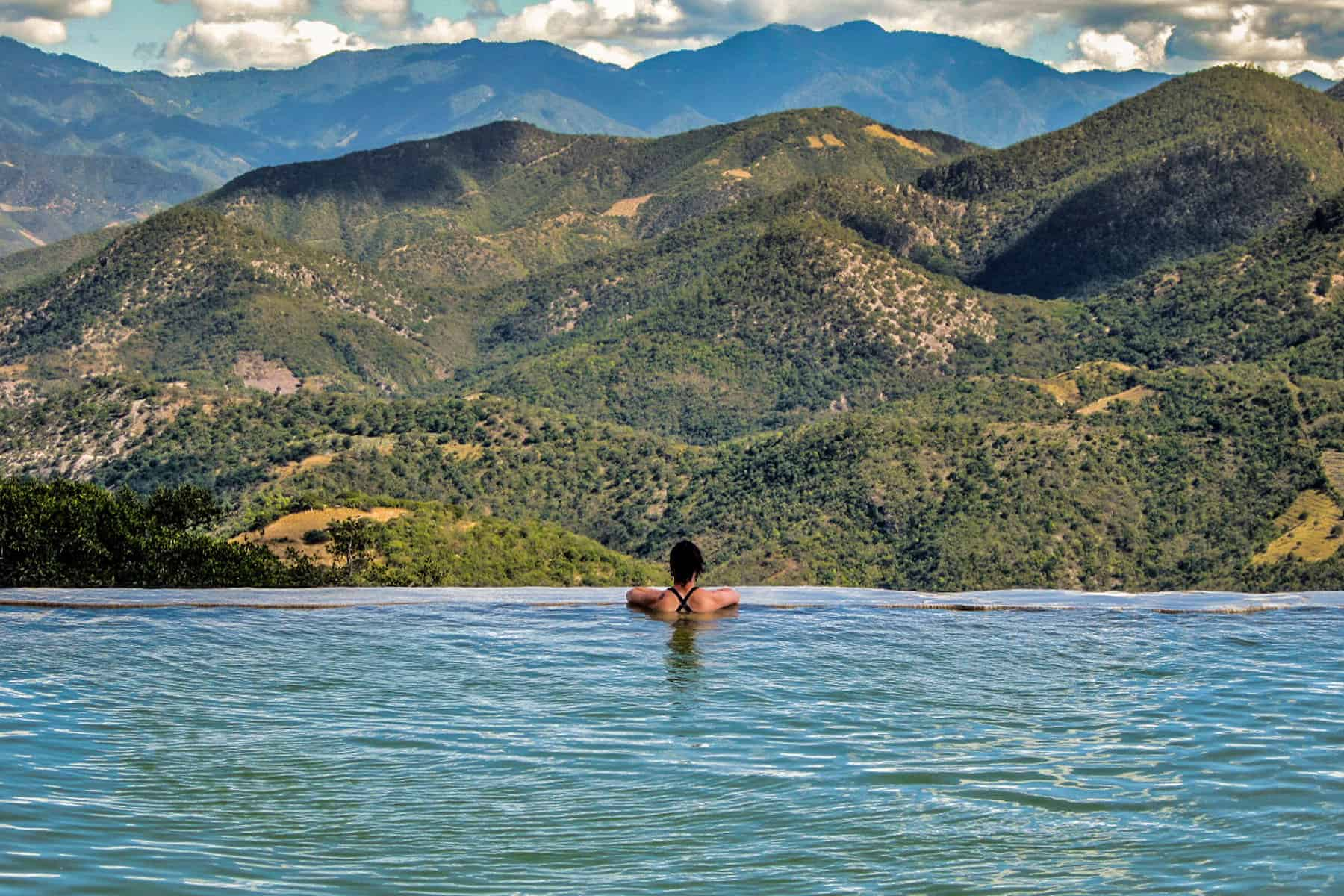 Girl in water overlooking a large valley at Hierve el Agua Mexico
