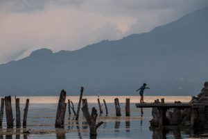Old tree stumps and a dock at dusk. A child stands on the dock at Lake Atitlan.