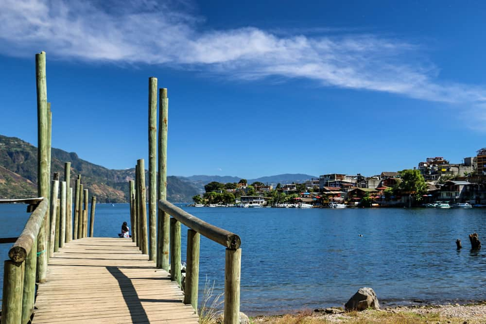 Wooden dock over the blue water of Lake Atitlan, with a colourful village in the background.