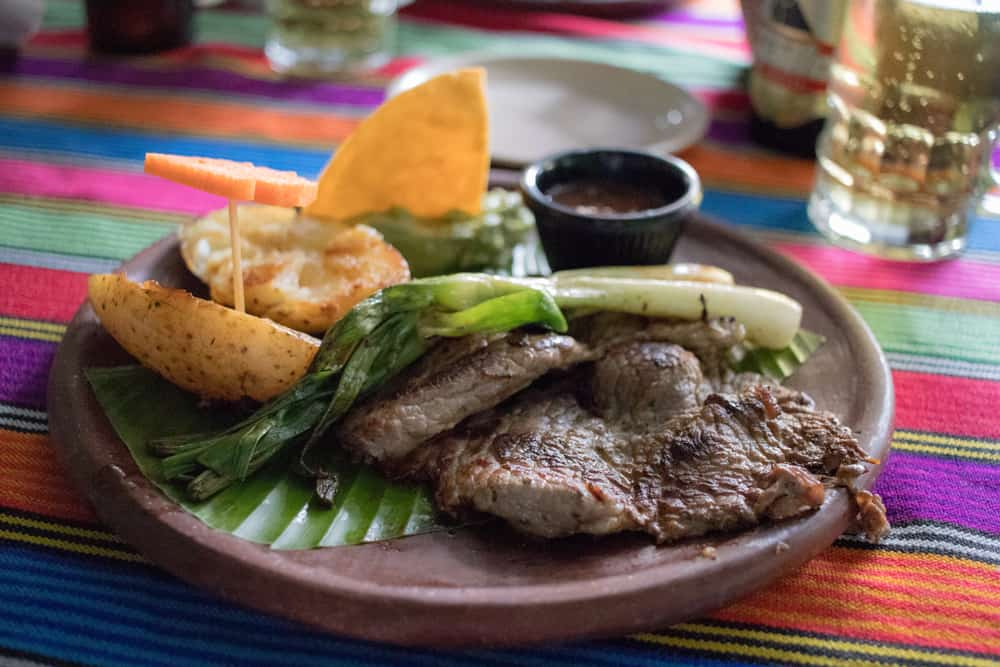 Plate with grilled meat, potatoes and onions on colourful tablecloth from an authentic Guatemalan restaurant in Antigua.