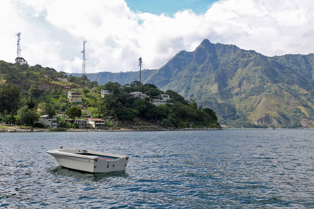 Boat in a lake with a green, tree-covered mountain in the distance at Lake Atitlan