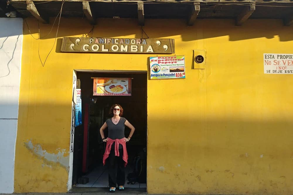 Girl in the doorway of a yellow building.