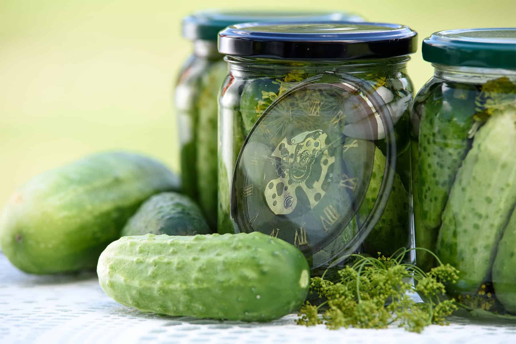 Pickles beside a pickle jar holding a pocket watch