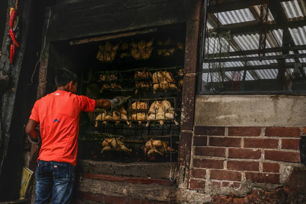 Man working in front of a large rotisseie full of chicken in Guatemala