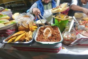 Woman at a street food stall in Antigua putting roasted pork on a sandwich.