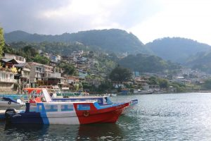 Red, white, and blue boat in the water, with a colourful village of San Pedro in the background