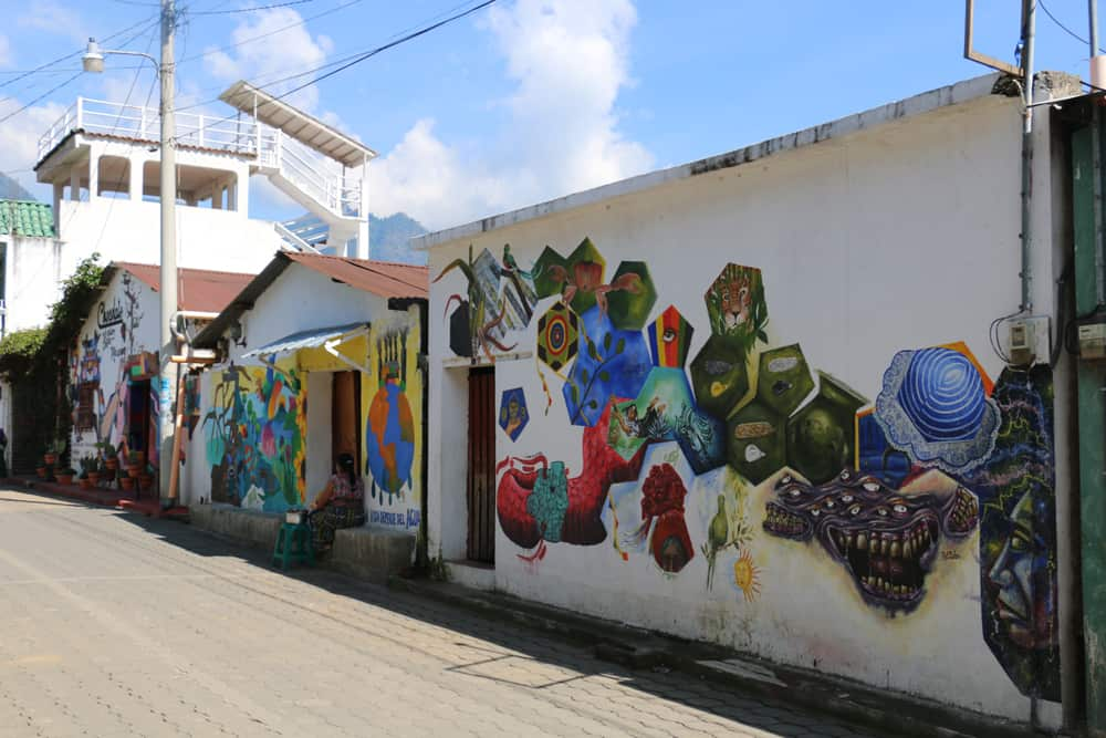 White walls covered in intricate patterned street art beside a chocolate shop in San Juan la Laguna.