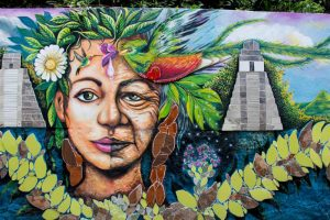 Colourful street art. Half young woman, half elderly, with Maya ruins in the background.