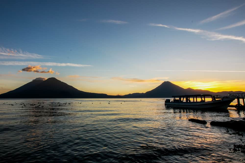 Sunset over Lake Atitlan with a boat in the foreground and two volcanoes in the back.