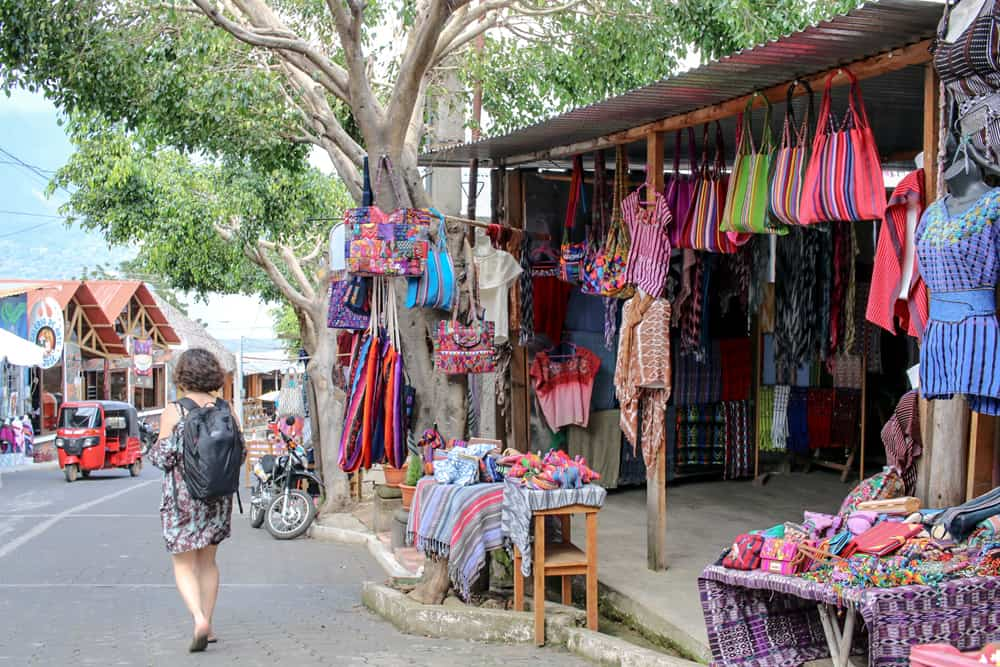 Woman walks passed a textile shop full of coloured clothing in San Juan Lake Atitlan
