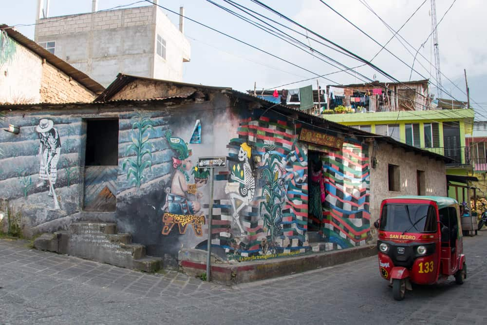 Red moto-taxi passes a builing covered in street art.