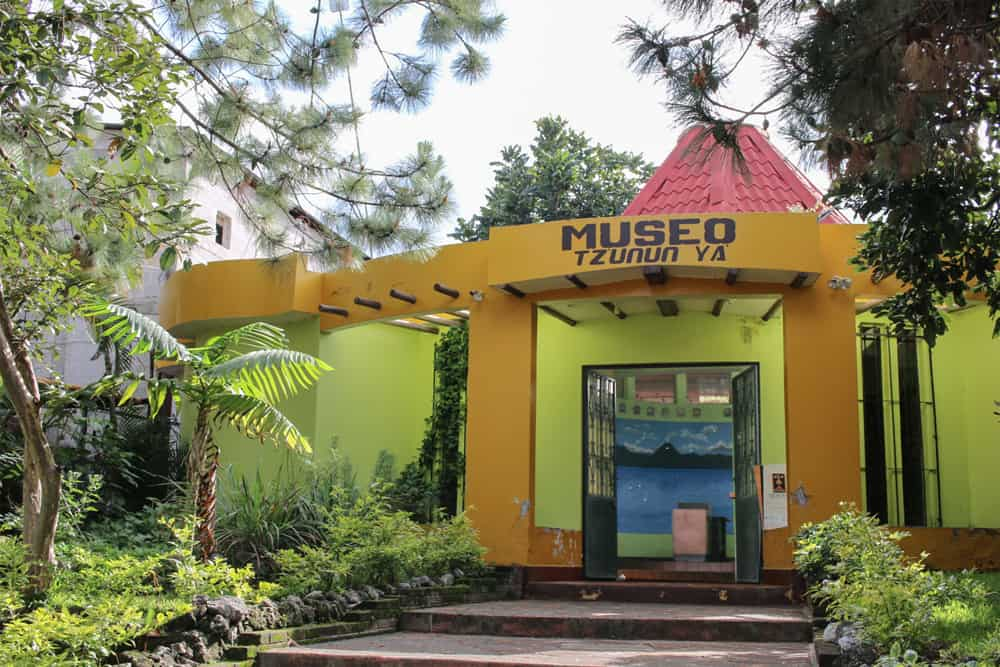 Yellow and green building, the front of Tz'unun Ya museum in San Pedro