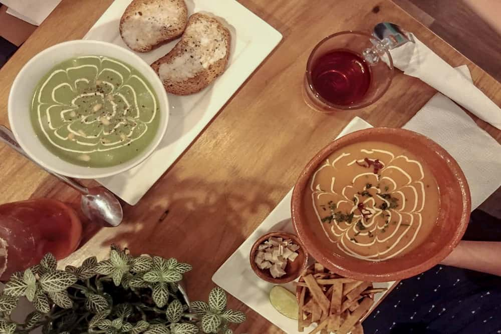 Two plates, one with a green soup and toast; the other with an orange soup with tortilla strips. This from a vegan restaurant in Antigua Guatemala.