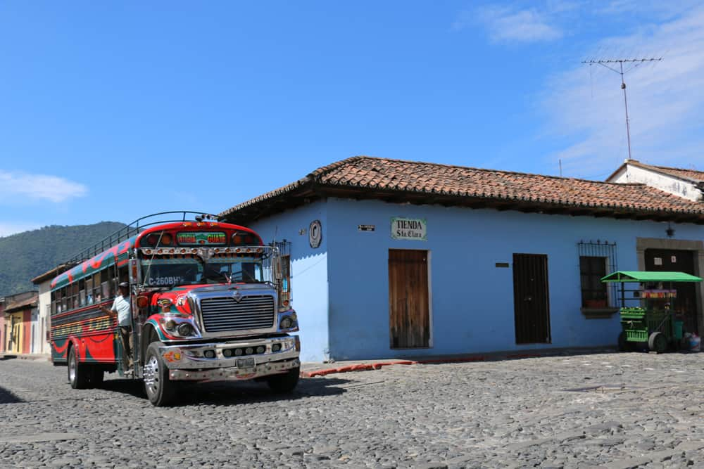 Red school bus with chrome and a blue building. Chicken bus from Antigua to El Tunco