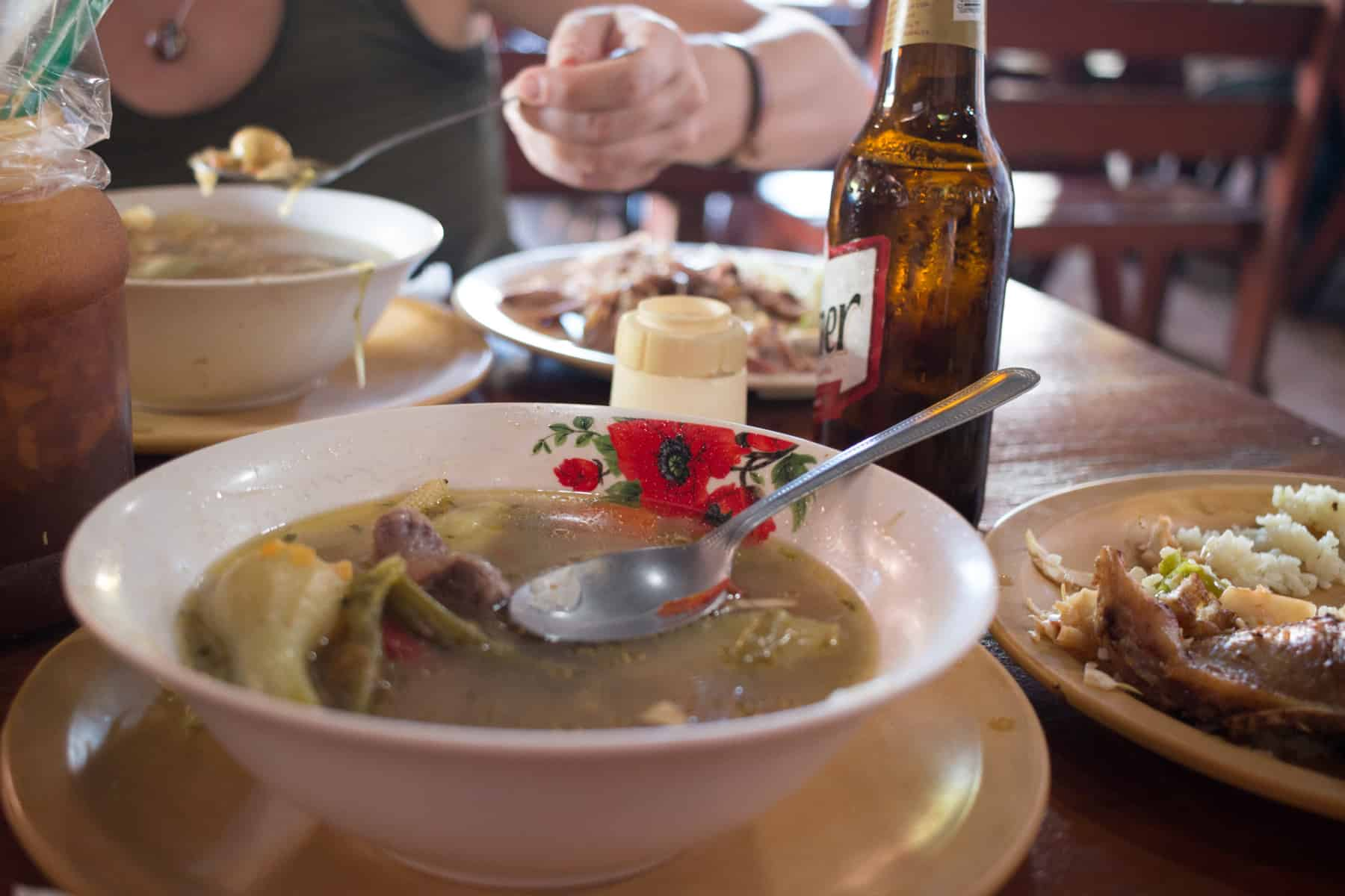 Two bowls of soup filled with broth and vegetales, with two other plates of rice and chicken, El Salvador Mondongo Soup