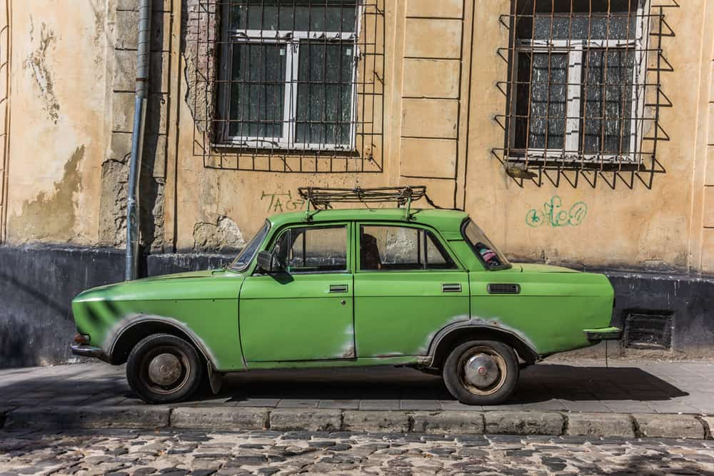 An old yellow car on the street in Romania