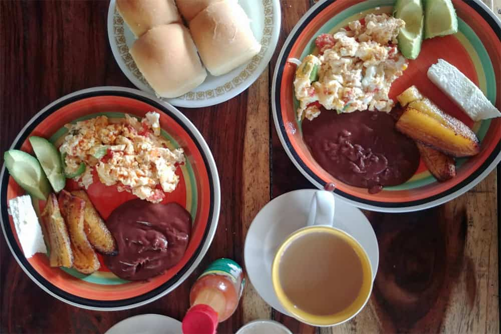 Two plates of breakfast with cups of coffee