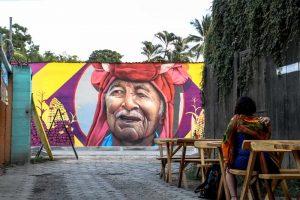 Woman sits at a table looking at colourful graffiti of a man in front of her in El Tunco.