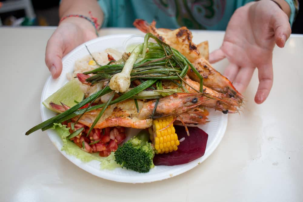 White plate with grilled vegetables and prawns being held by two hands