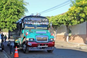 Green and red school bus on the side of the road with the words Santa Ana and Juayua in the window