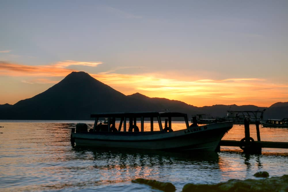 Sun setting over a volcano with a Lake Atitlan and boat in the foregroundhe foreg