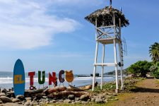 "Sign that says ""El Tunco"" beside a wooden tower"