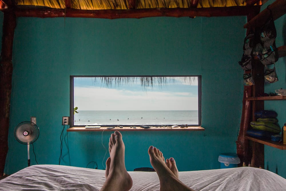 Feet on a bed and a window on the wall