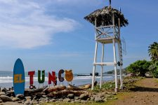 "Wooden watchtower beside a sign that reads ""El Tunco"" with a beach in the background"