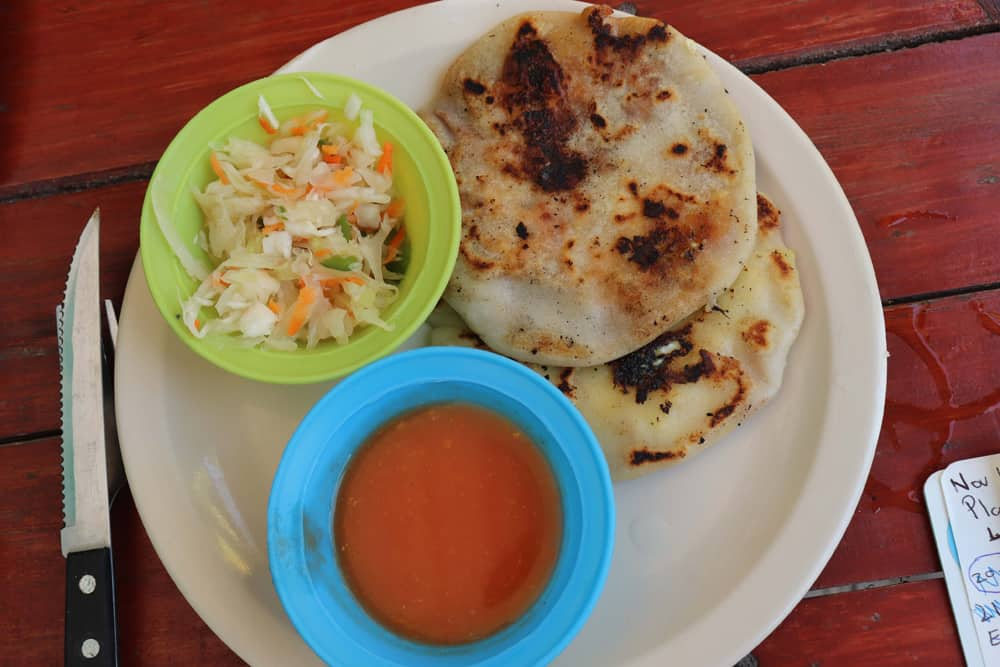 Pupusas on a plate with a blue container of tomato sauce and a green container of slaw