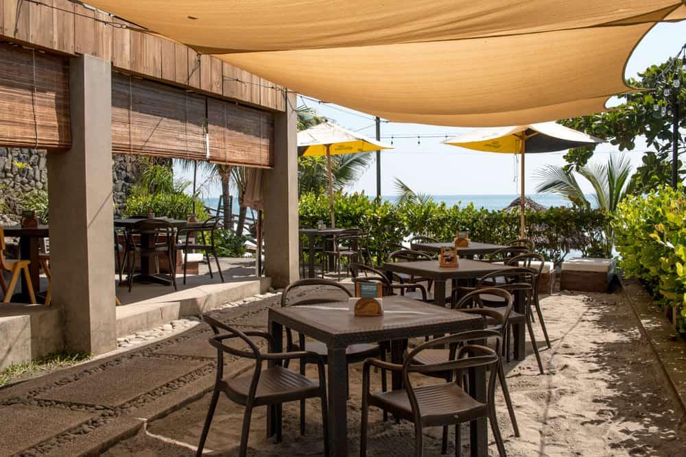 Tables under a canopy near the beach