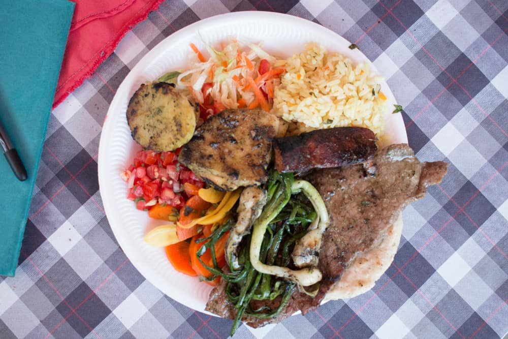 White plate on a checkered tablecloth. On the plate from the food festival is grilled vegetables, rice, potatoes and a steak