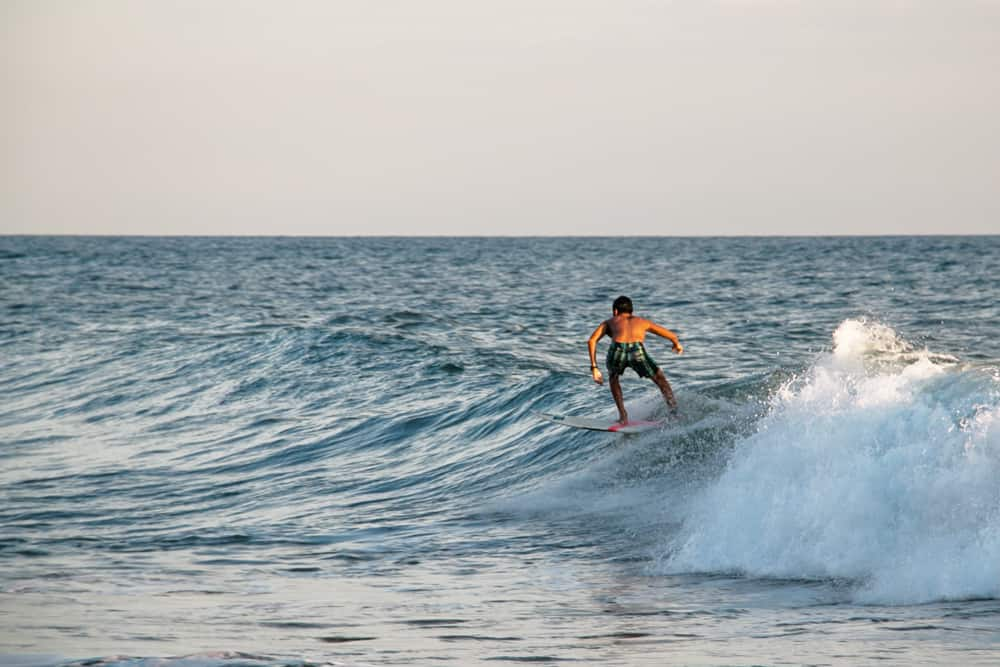 Surfer rides a wave in El Salvador