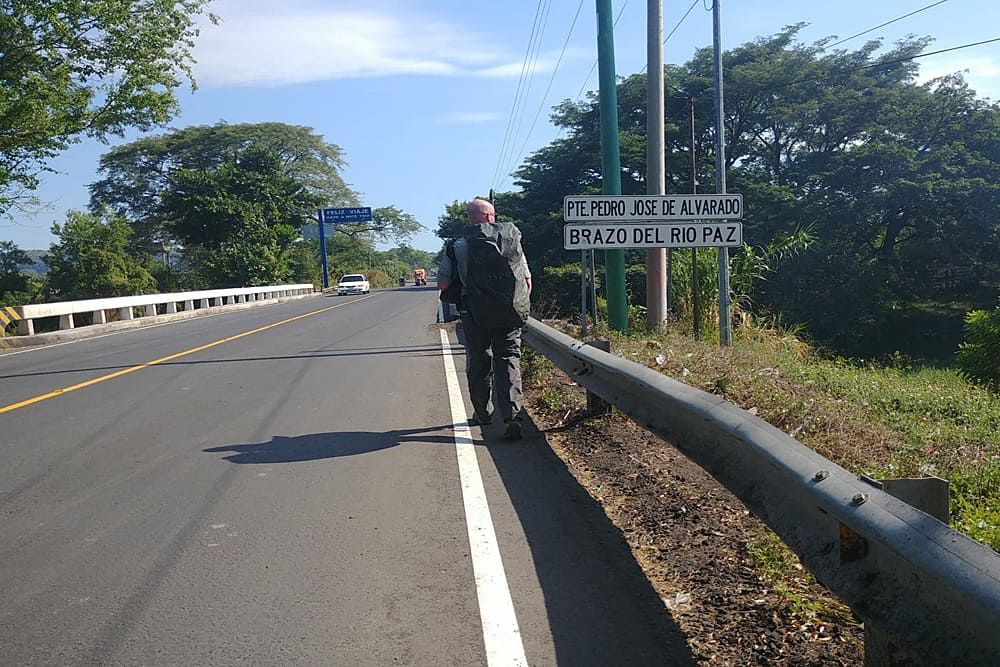 Man walking across a bridge looking at a sign in Spanish at the Guatemala El Salvador border crossing.