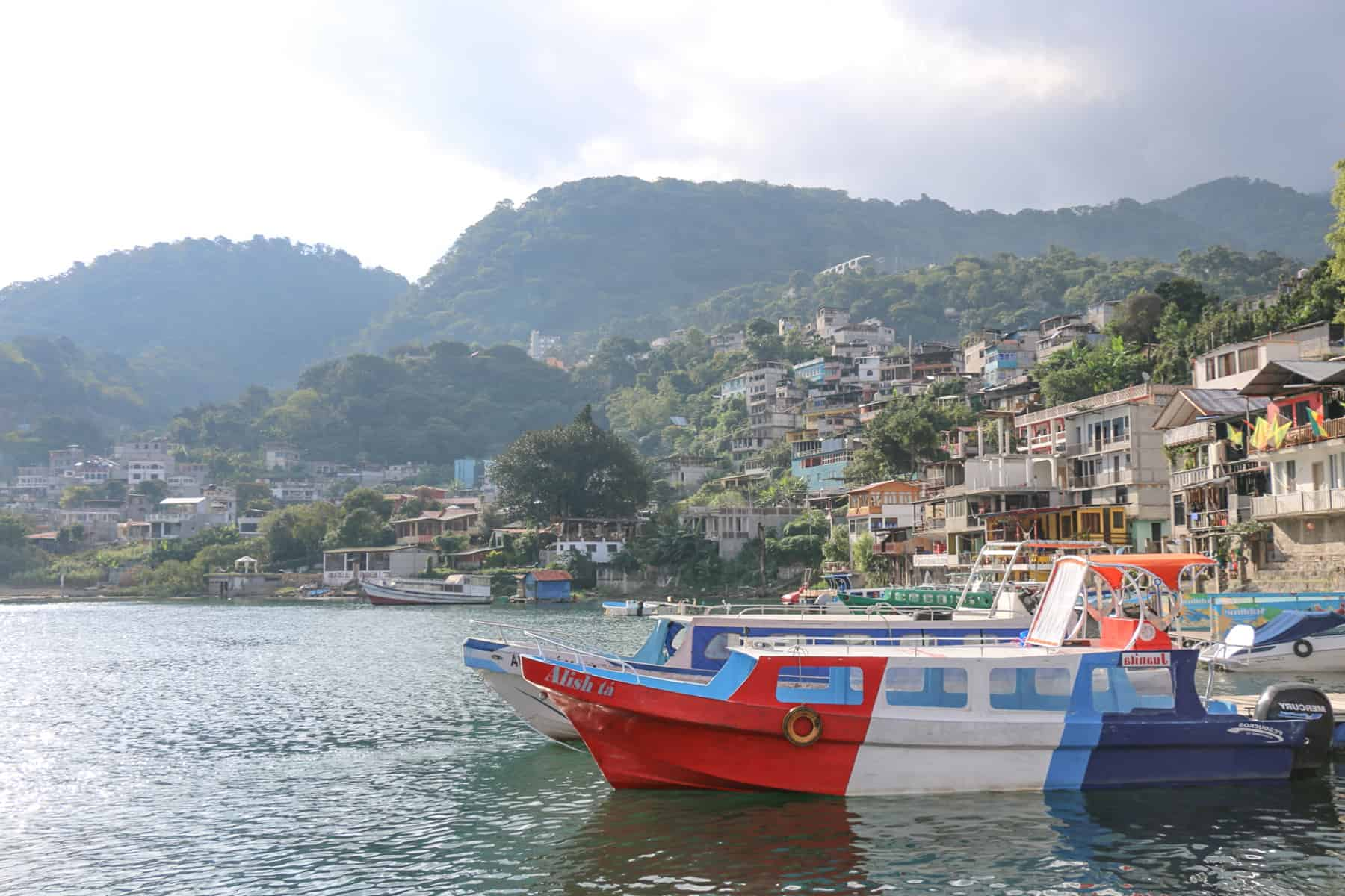 Red white and blue boat in the water with a village behind it at Lake Atitlan