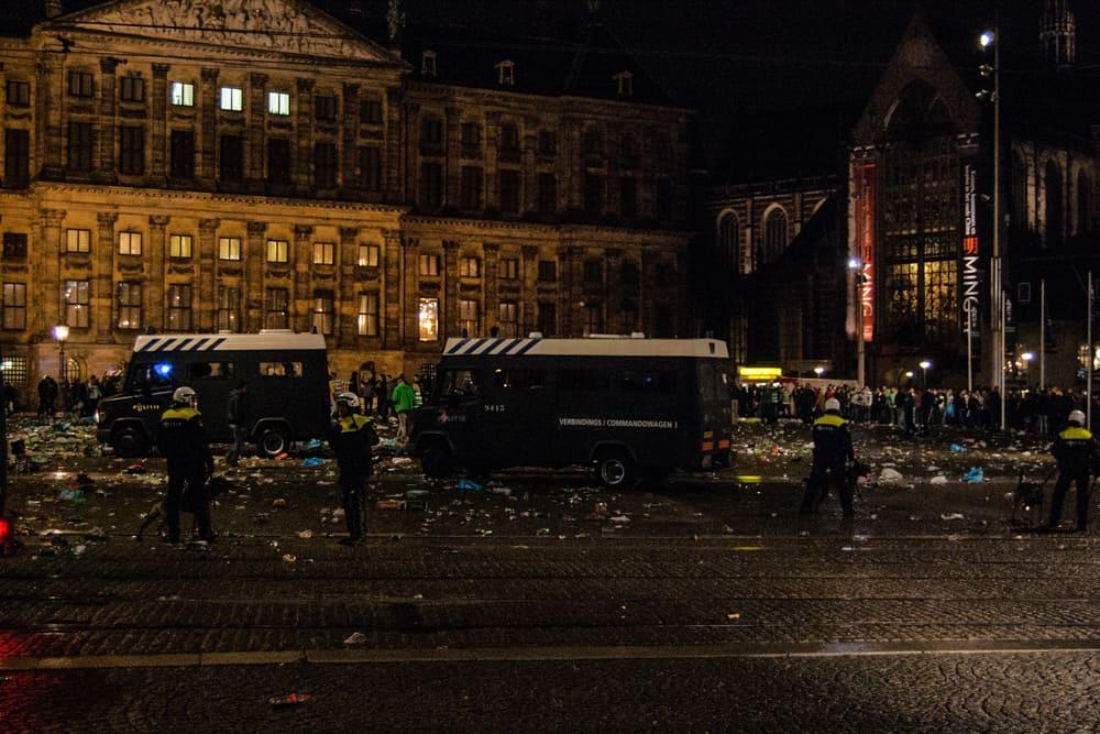 Police vans and police standing near broken bottles