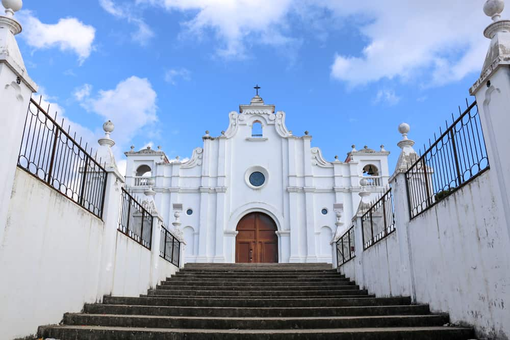 Grey steps lead to a white church with a brown door in Apaneca.