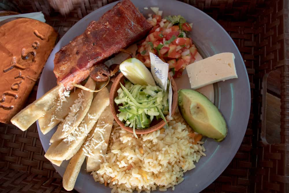 Plate of food including rice, potatoes, salad, cheese and pork. From a restaurant ruta de las flores