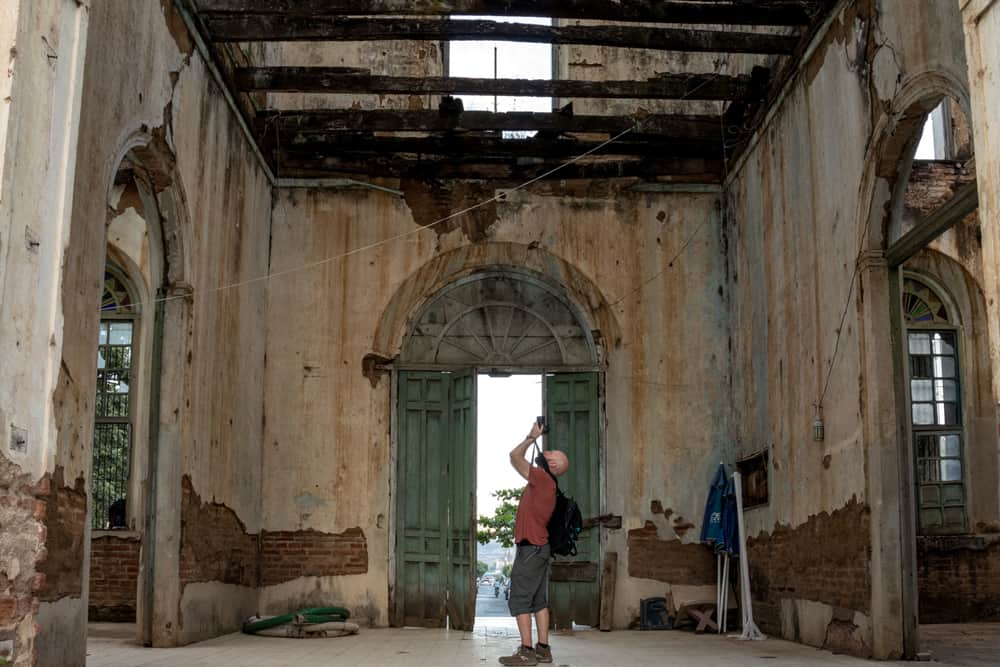 Man taking photo inside a ruined buildin