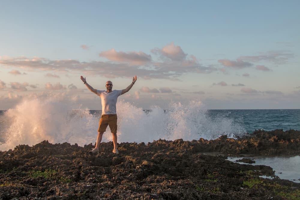 Man standing on rocks with waves splashing behind him