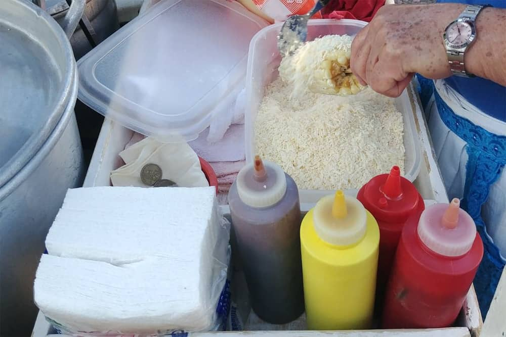 Sauce bottles and powdered chees being put on corn
