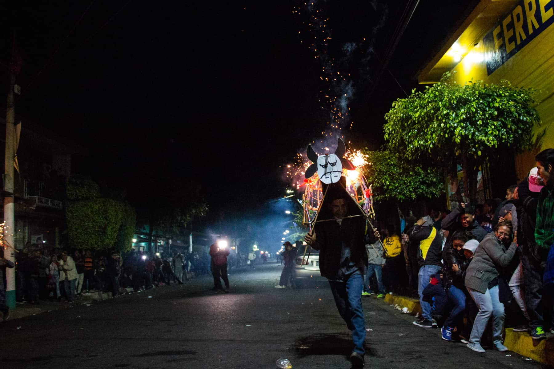Man running down the street with a cardboard bull costume shooting fireworks in El Salvador
