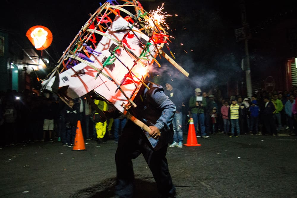 Man holding wooden bull costume shooting fireworks on the street