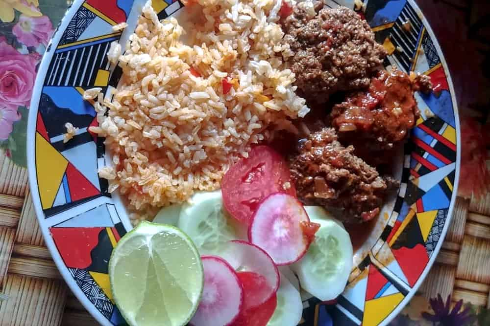 Cucumbers, tomatoes, meatballs and rice on a plate