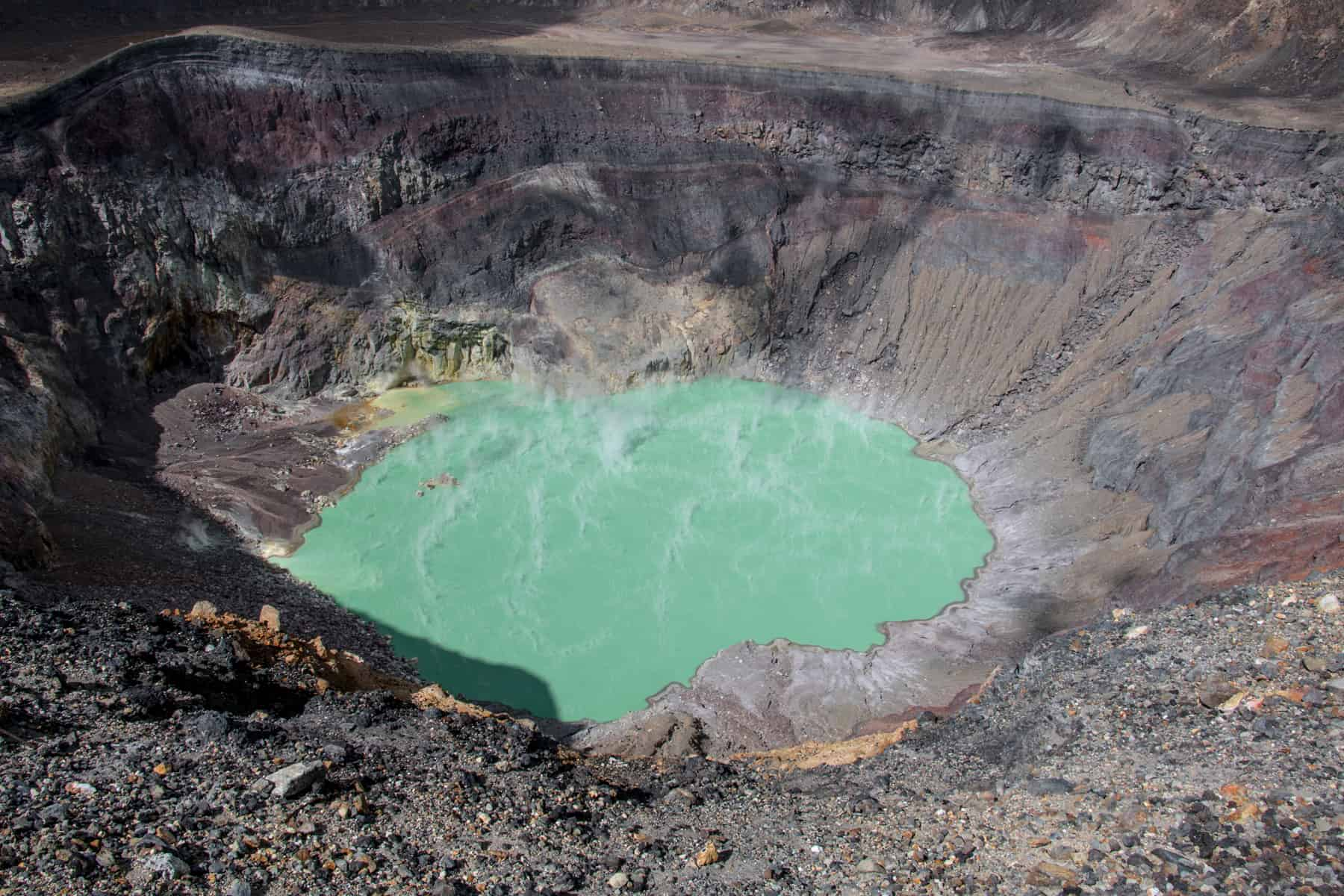 Turquoise lake with steam surrounded by rocks and dirt at Santa Ana Volcano El Salvador