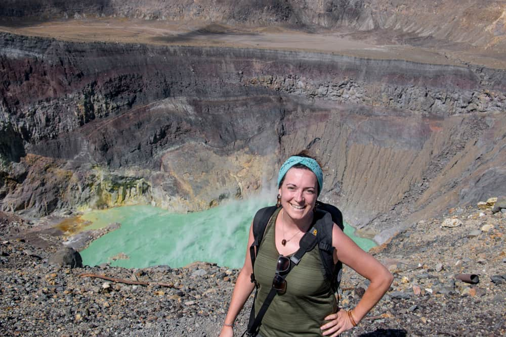 Girl smiling with a green volcano crater lake behind her at the Santa Ana Volcano El Salvador