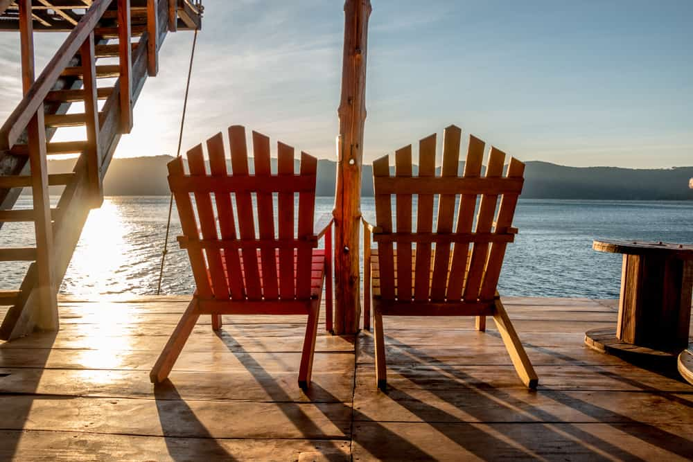 Two chairs on a deck in front of a lake at sunset
