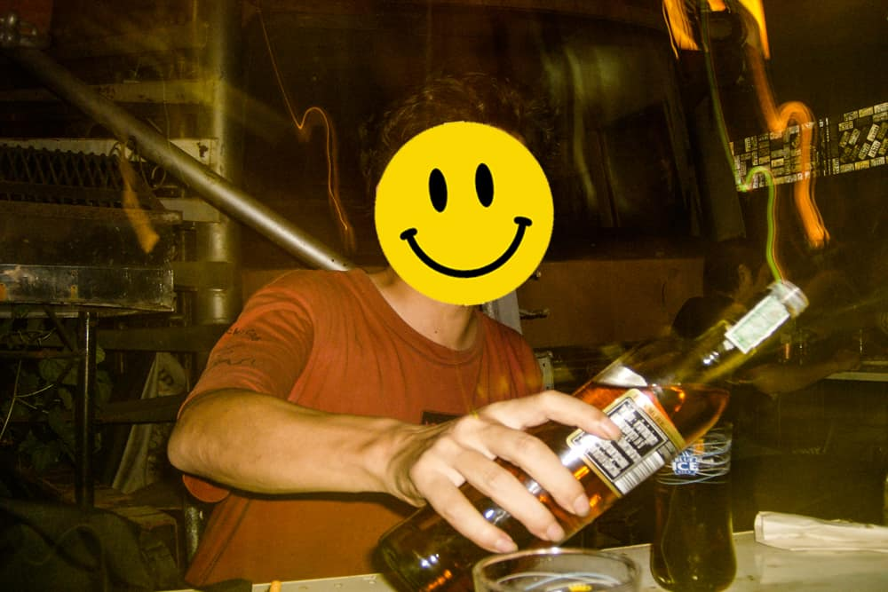 Person pouring whiskey into a glass, a fake smiley face over the real face