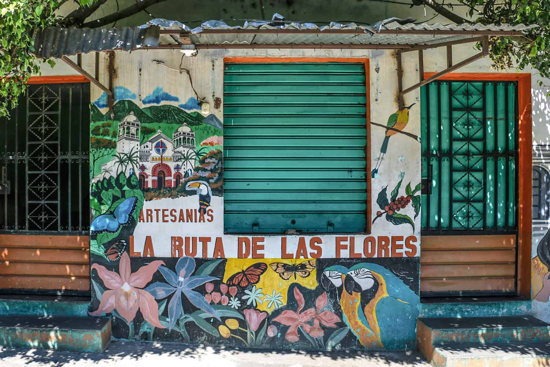 Colourful building front with green shutters and graffiti flowers in the Ruta de Flores