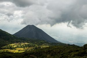 Volcano behind a green jungle with dark clouds overhead