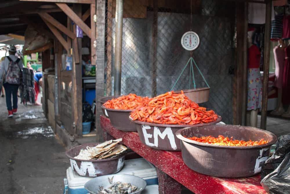 Orange prawns in brown pails in a market in San Miguel